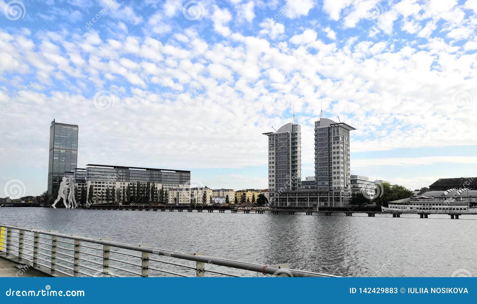Berlim moderna: construções bonitas, escultura do homem da molécula e céu nebuloso