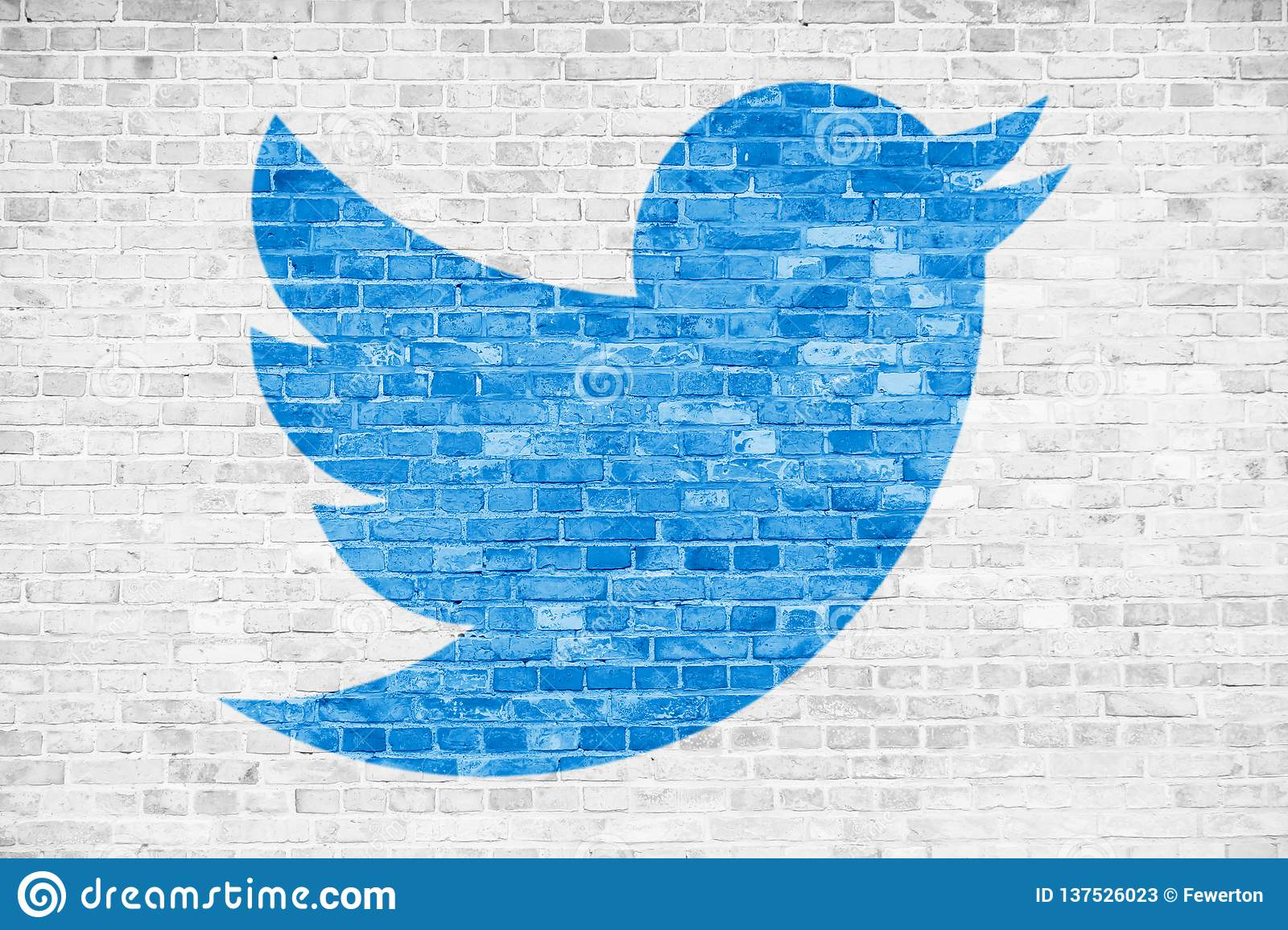 Twitter social media blue bird sign logo symbol in minimalist design painted over white brick wall background