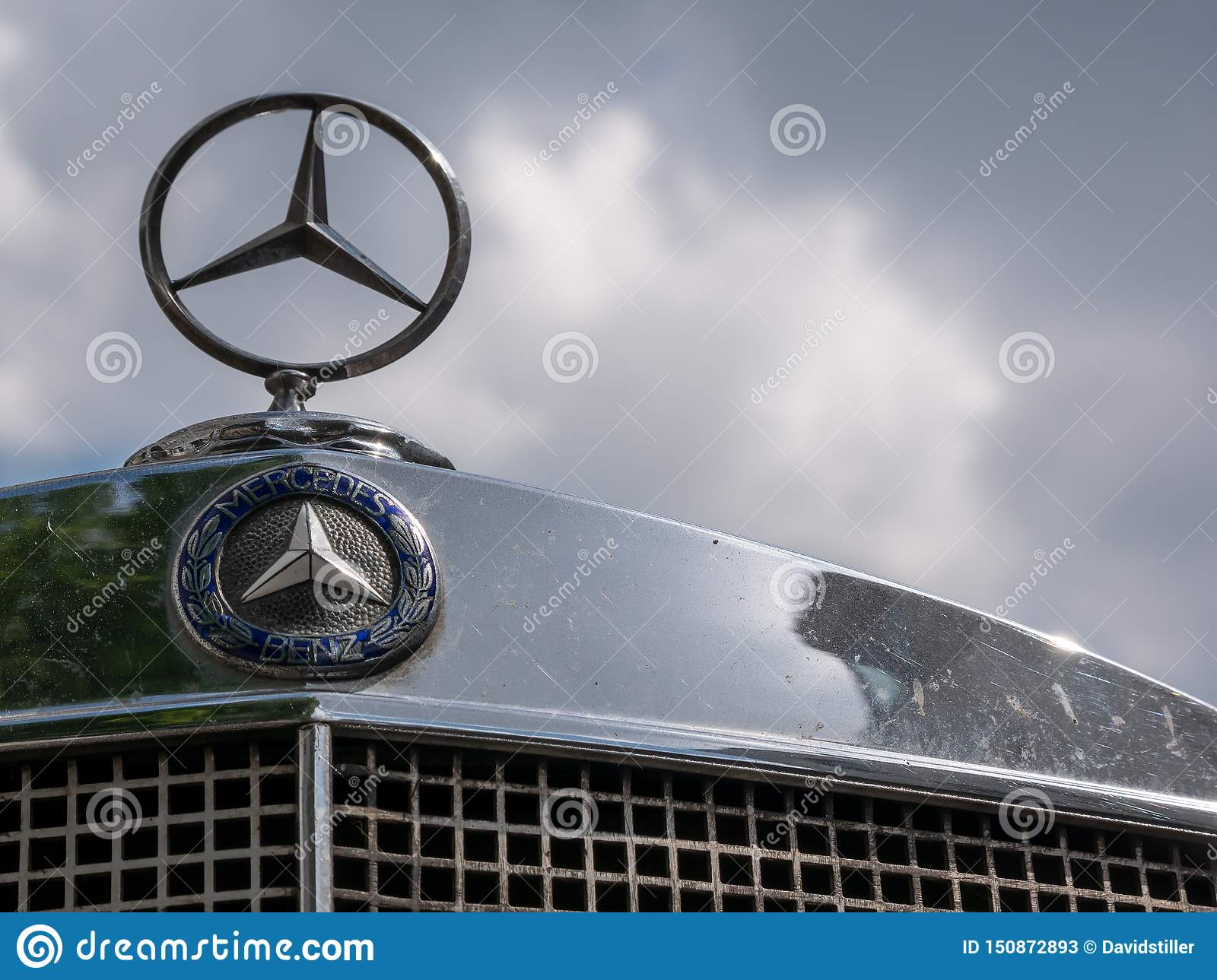 Mercedes Logo And Star On A Mercedes Vintage Car Against A Cloudy Sky