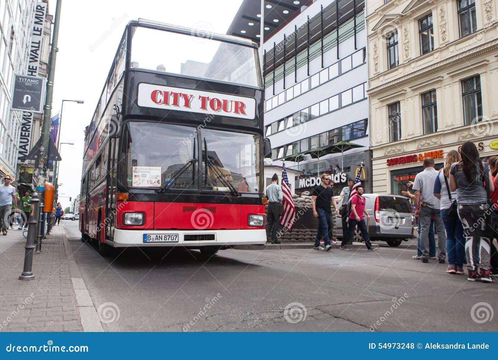 BERLIN TYSKLAND - MAJ 10, 2015: Buss på Checkpoint Charlie Korsningen punkt mellan östligt och västra - berlin blev ett symbol av