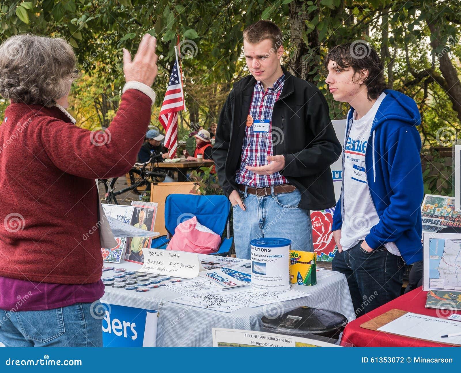 Bernie Sanders-de vrijwilligers spreken met vrouw bij de informatie van de Landbouwersmarkt