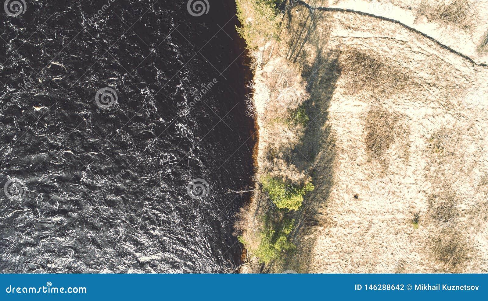 ?berraschender Luftschu? des sch?nen dunklen Flussufers Herbstrandauslegung mit Eicheneicheln und -tageslicht