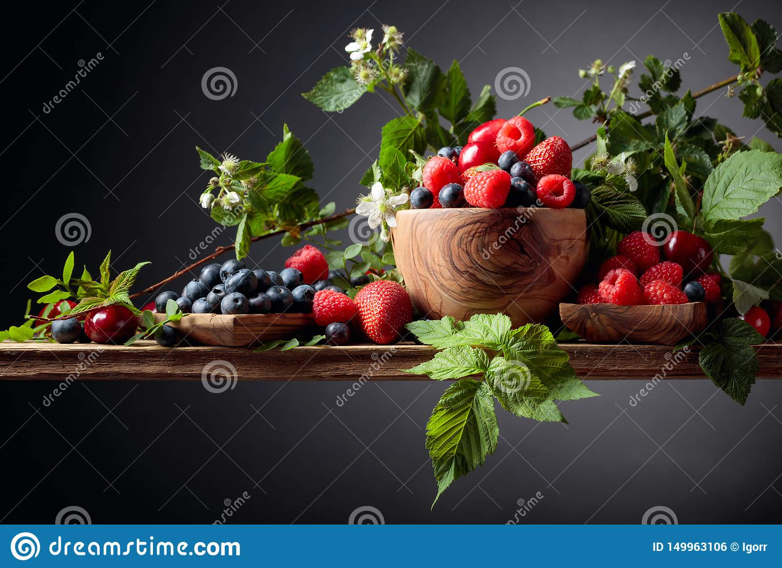 Berries closeup colorful assorted mix of strawberry, blueberry, raspberry and sweet cherry on a old wooden table