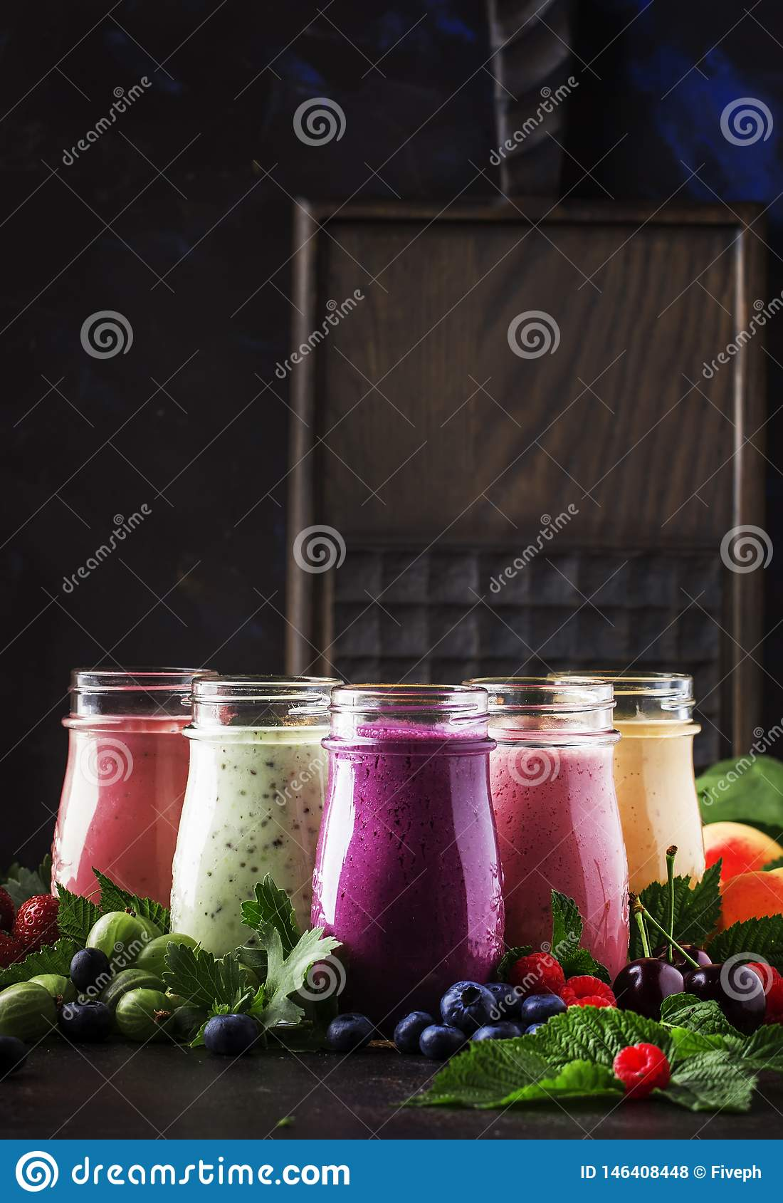 Berry fruit cokctalis, smoothies and milkshakes, fresh fruit and berries on brown table, still life, selective focus