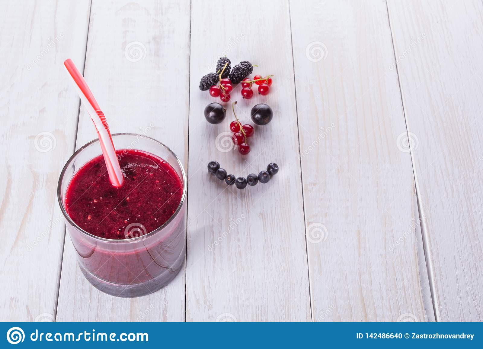 Berry smoothie in a glass jar with a straw, over vintage wood table with fresh mulberry berries, blackberries and currants. Smile