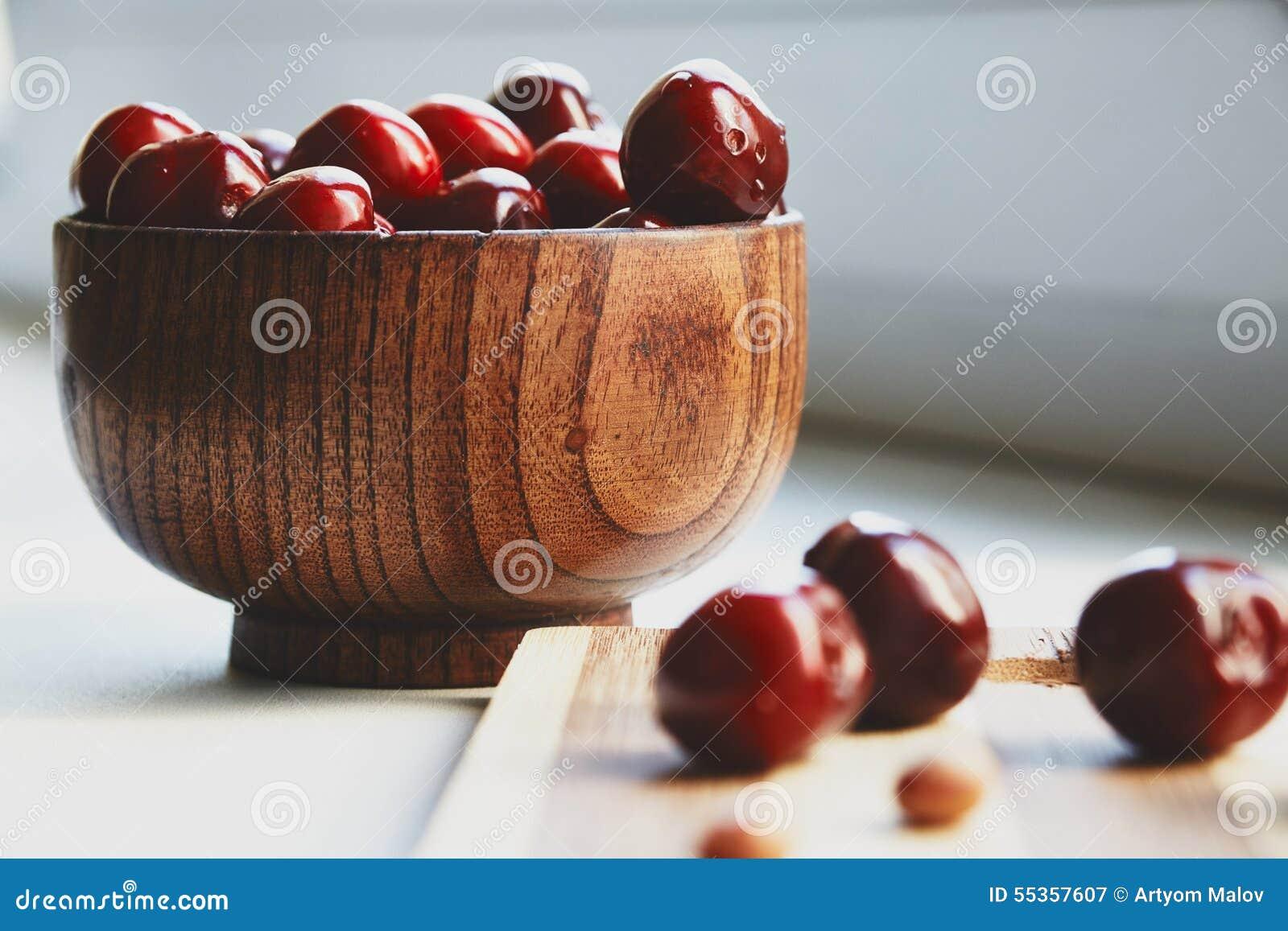 Berryes della ciliegia nella ciotola di legno