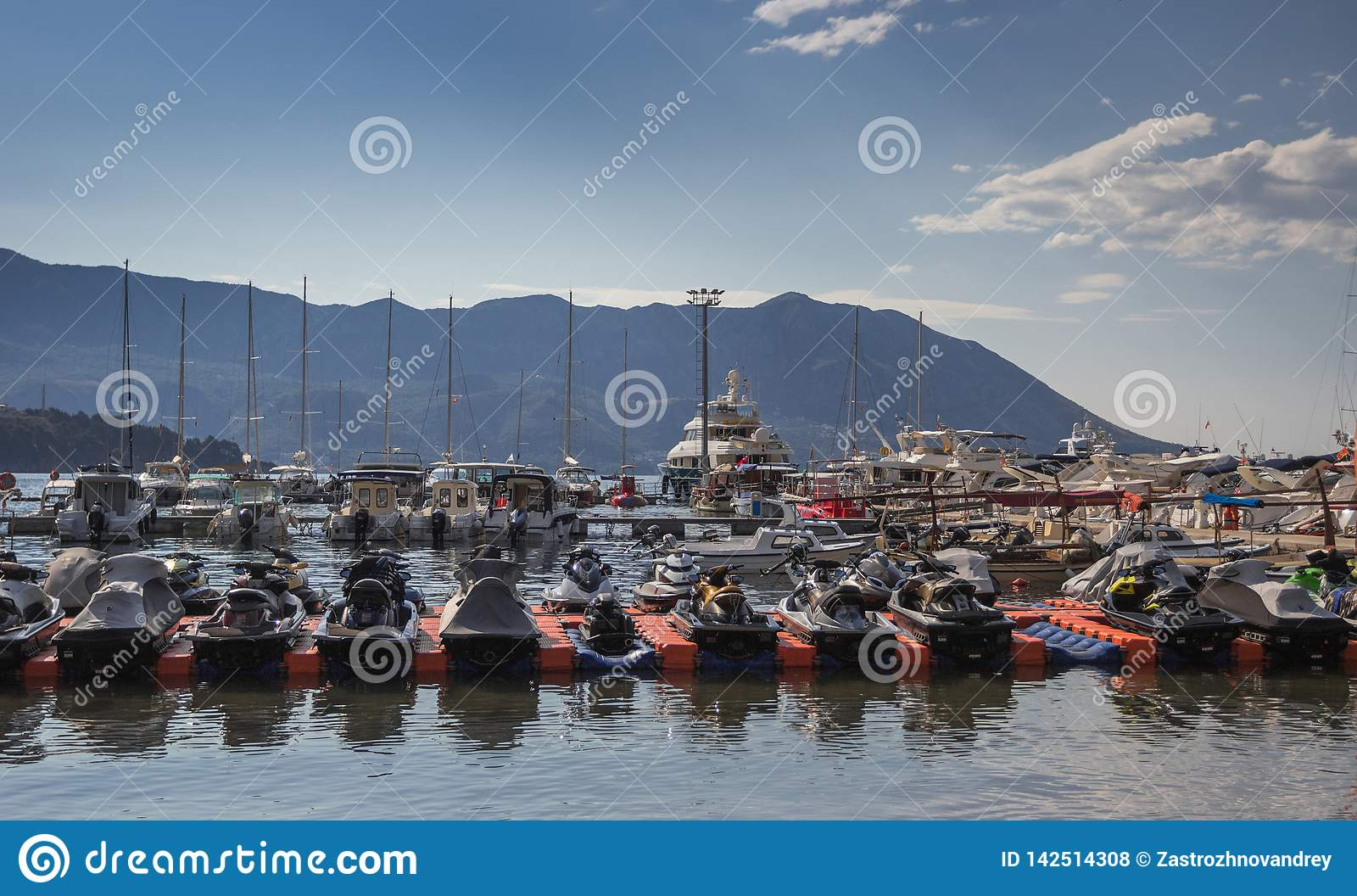 Berth with standing yachts and jet skis on a background of mountains