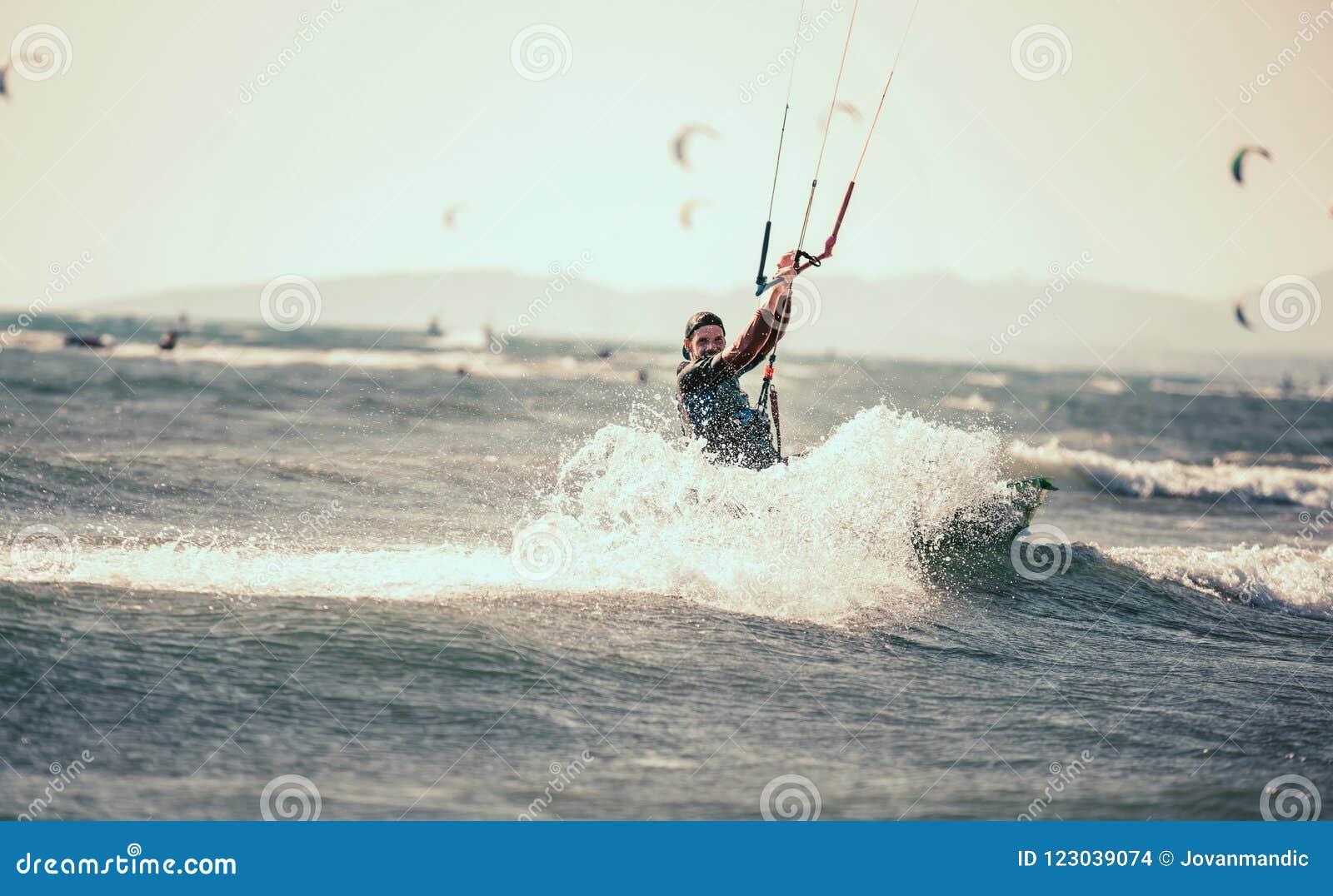 Berufs-kiter macht den schwierigen Trick auf einem schönen Hintergrund