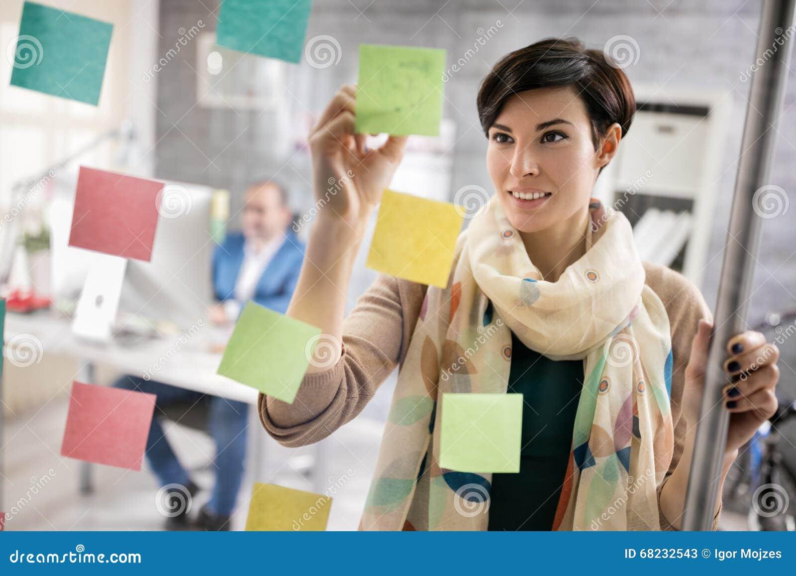 Berufstätige Frau macht Entwurf auf Aufklebern am Arbeitsplatz