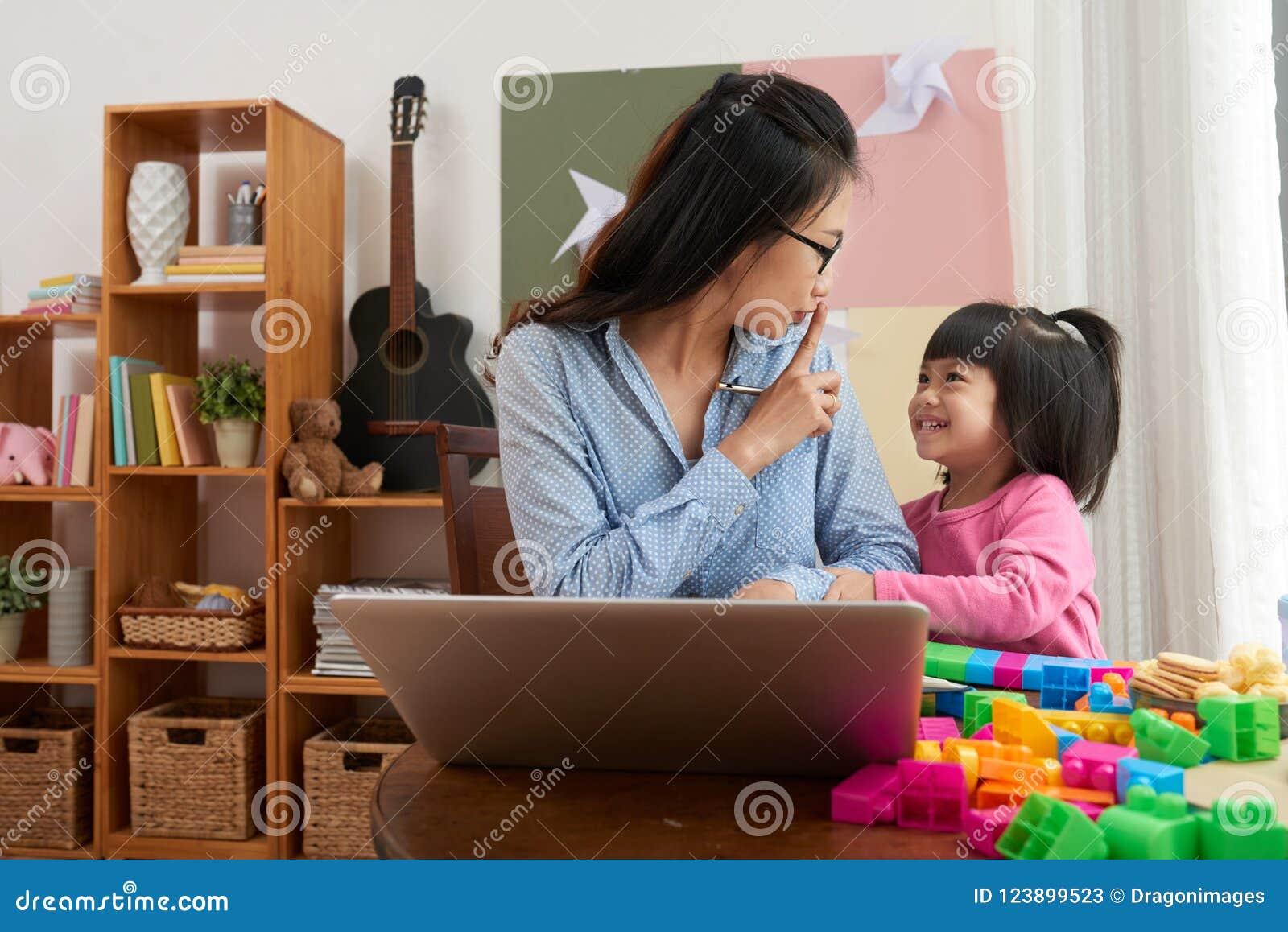 Berufstätige Frau mit spielerischem Mädchen zu Hause