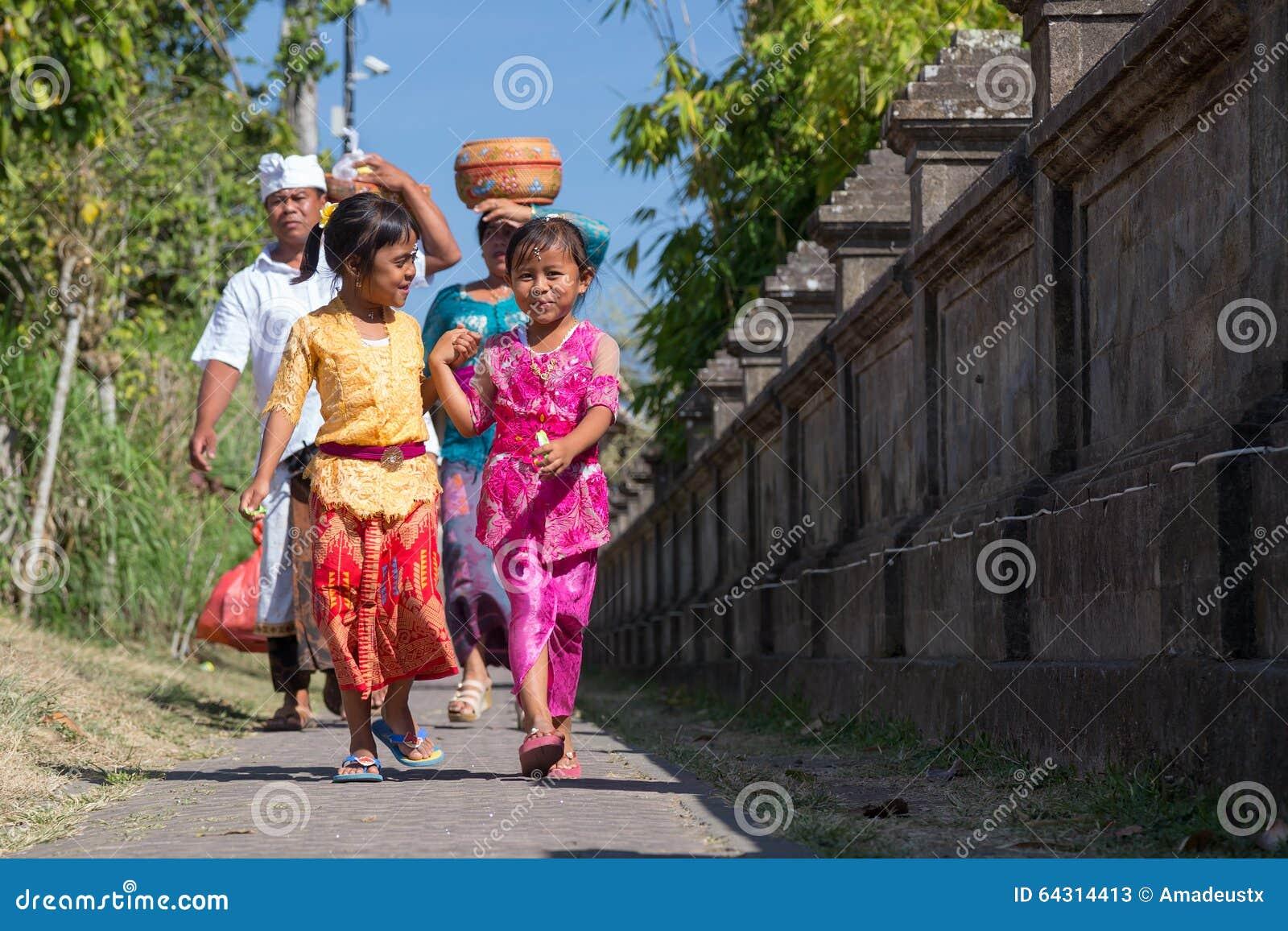 Besakih,巴厘岛/印度尼西亚村庄-大约2015年10月:愉快的家庭从节日回来在Pura Besakih