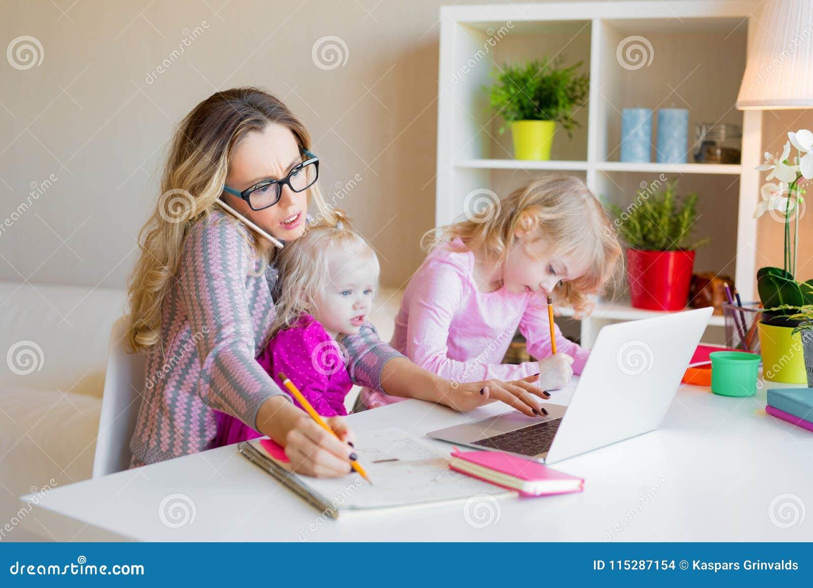 Beschäftigte Frau, die versucht beim Babysitten von zwei Kindern zu arbeiten