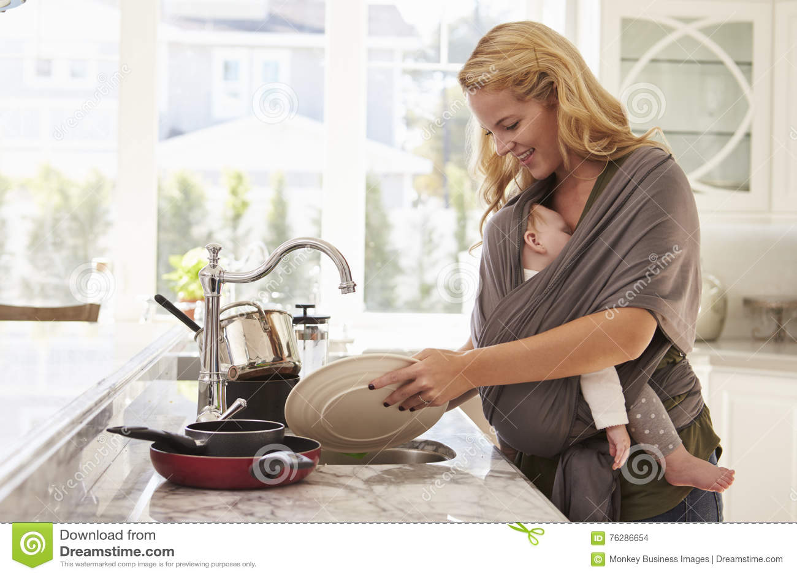 Beschäftigte Mutter mit dem Baby im Riemen zu Hause mehrere Dinge gleichzeitig tuend