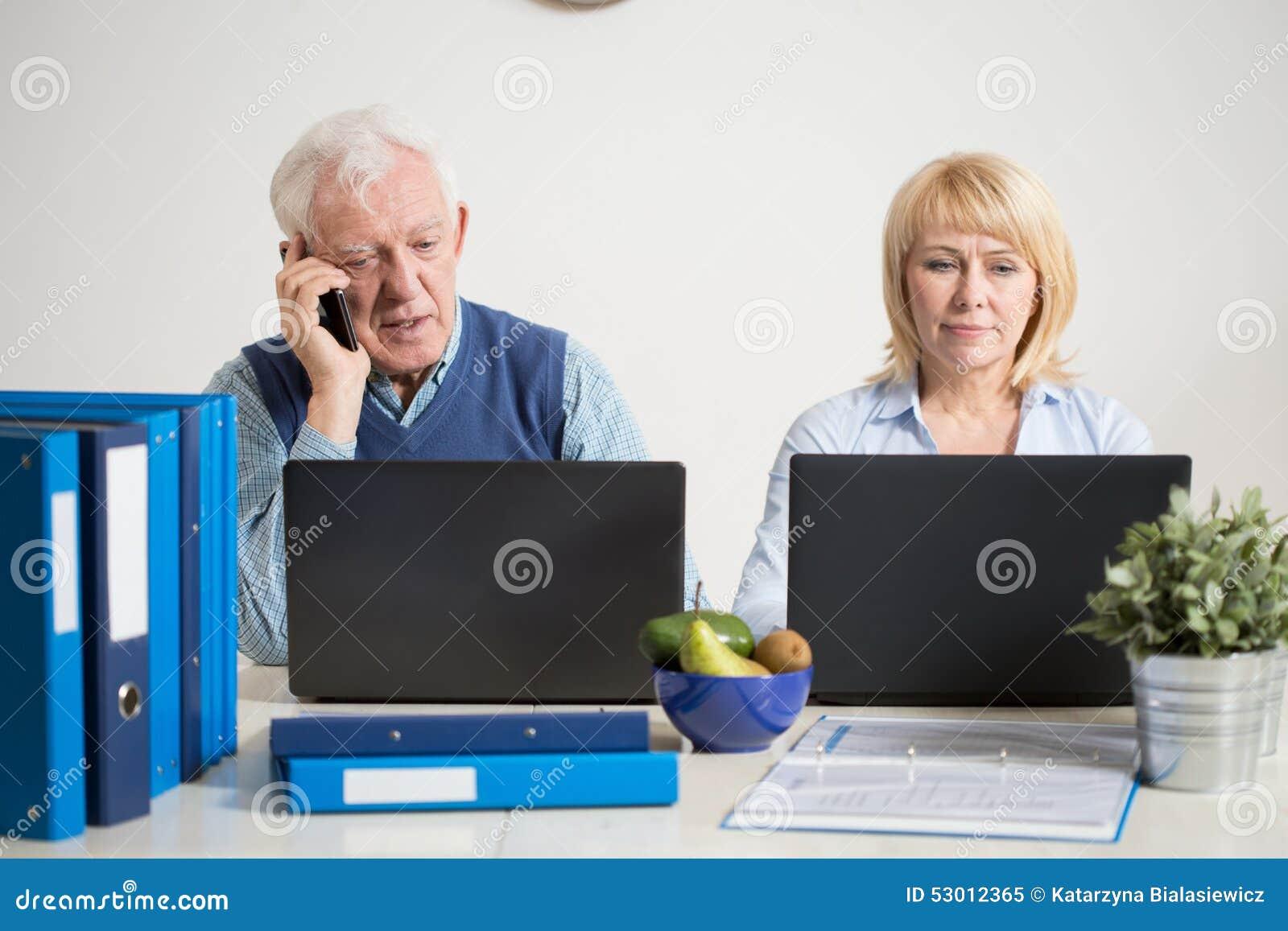Beschäftigte Paare unter Verwendung der Laptops