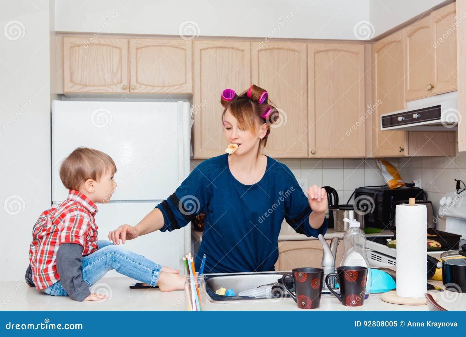 Beschäftigte weiße kaukasische Mutterhausfrau der jungen Frau mit Haarlockenwicklern in ihrem Haar kochend, Abendessenmahlzeit in