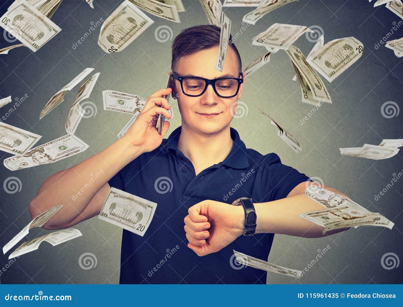 Beschäftigter Geschäftsmann, der die Armbanduhr, sprechend am Handy unter Bargeldregen betrachtet Zeit ist Geld Konzept