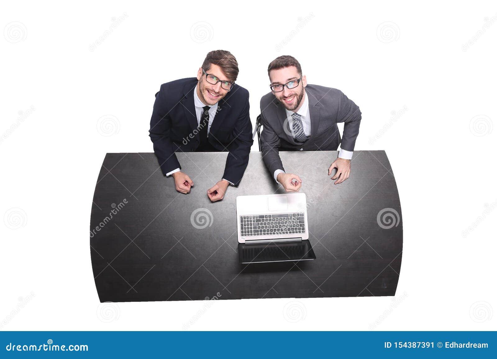 Beschneidungspfad eingeschlossen lächelnde Geschäftskollegen, die vor einem offenen Laptop sitzen
