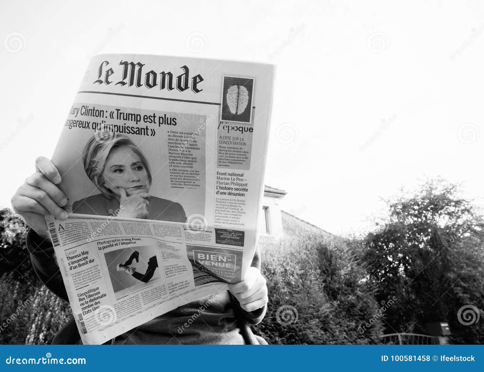 Beskåda underifrån av kvinnan som läser den senaste tidningsLe Monde med ståenden av Hillary Clinton