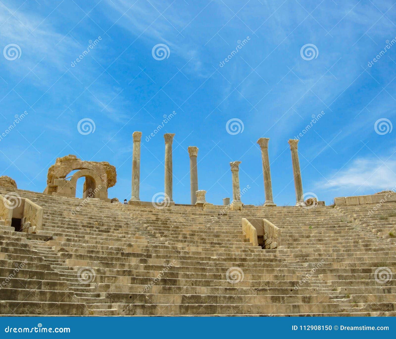 Beskåda upp trappan och visningställningarna till kolonner mot himmel på den forntida romerska teatern av Leptis Magna i Libyen