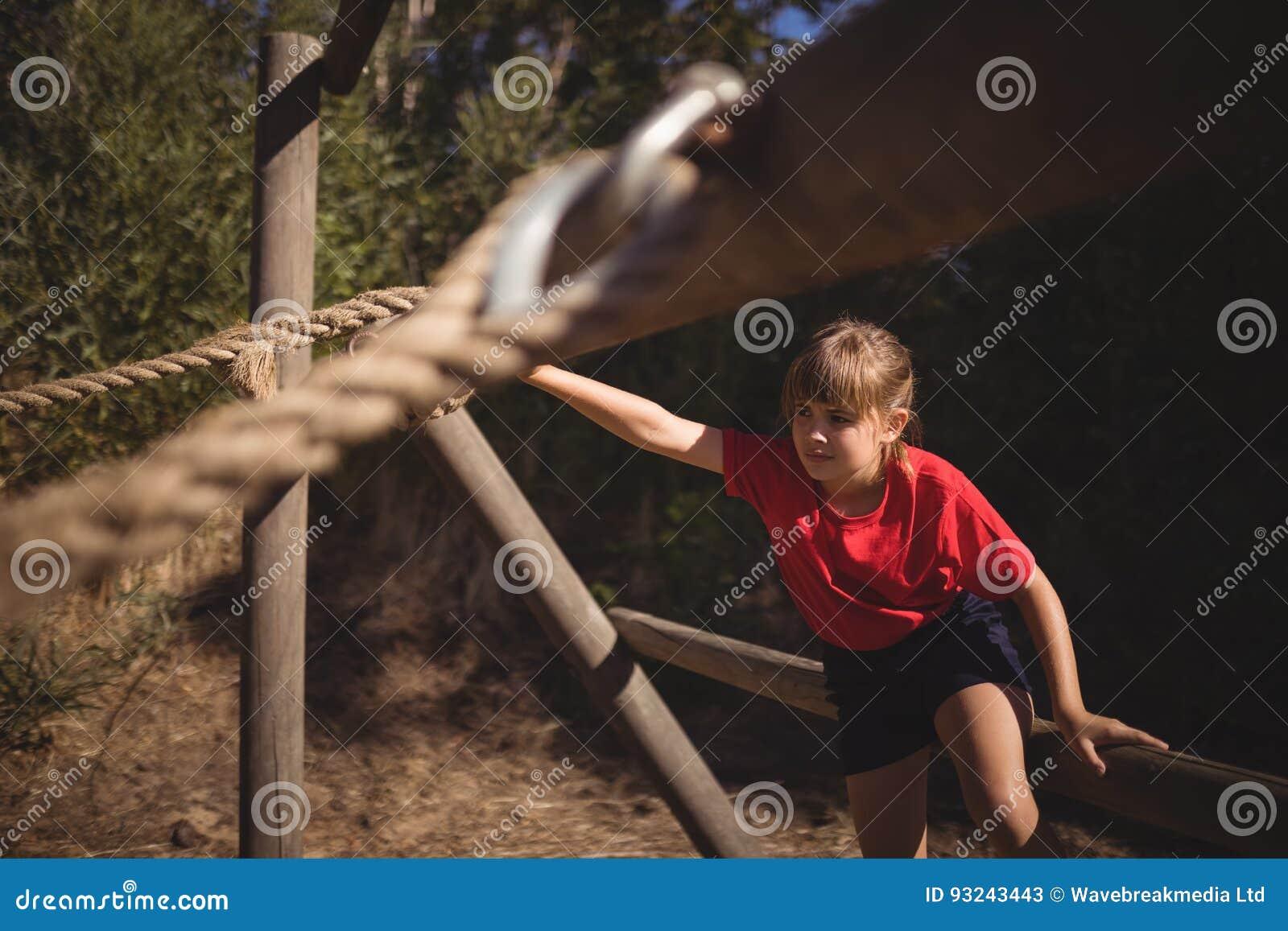 Beslutsam flicka som övar på utomhus- utrustning under hinderkurs