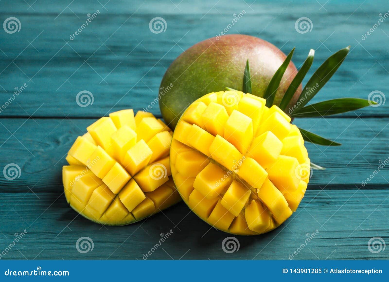 Besnoeiings rijp mango s en palmblad op houten achtergrond
