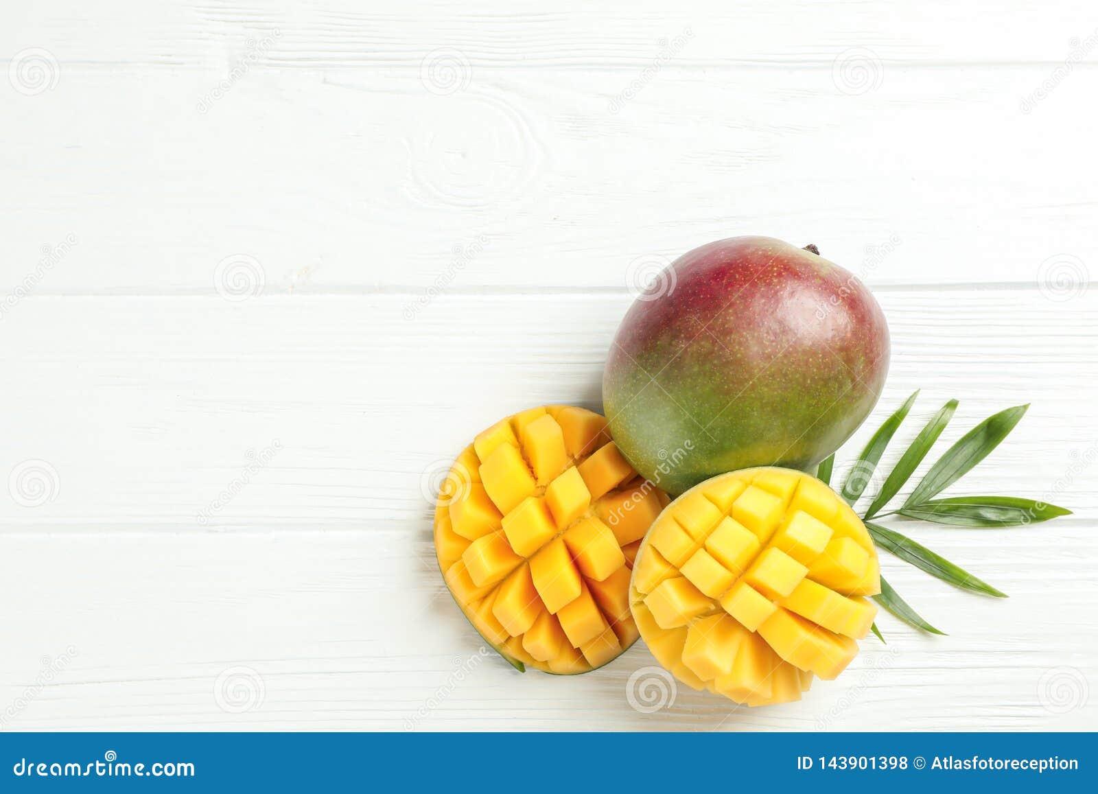 Besnoeiings rijp mango s en palmblad op witte achtergrond