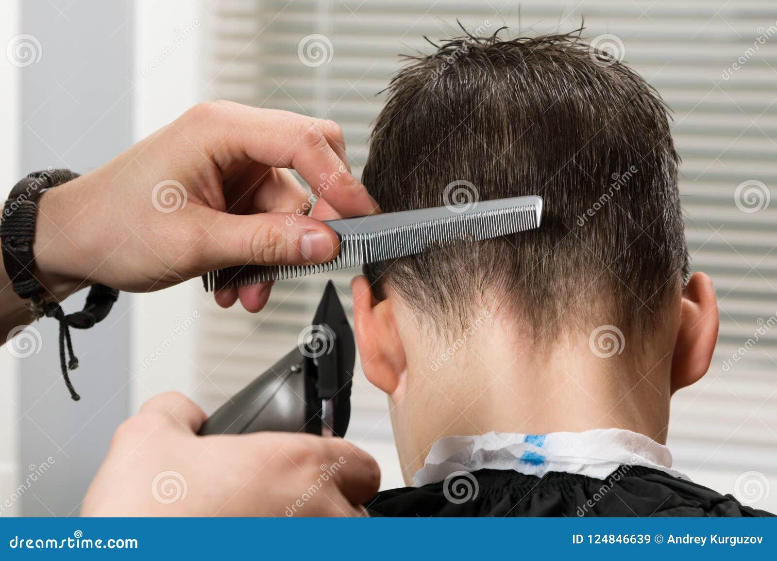 Besnoeiingshaar aan de jongen op het achterhoofd die haarclipper en een kam gebruiken