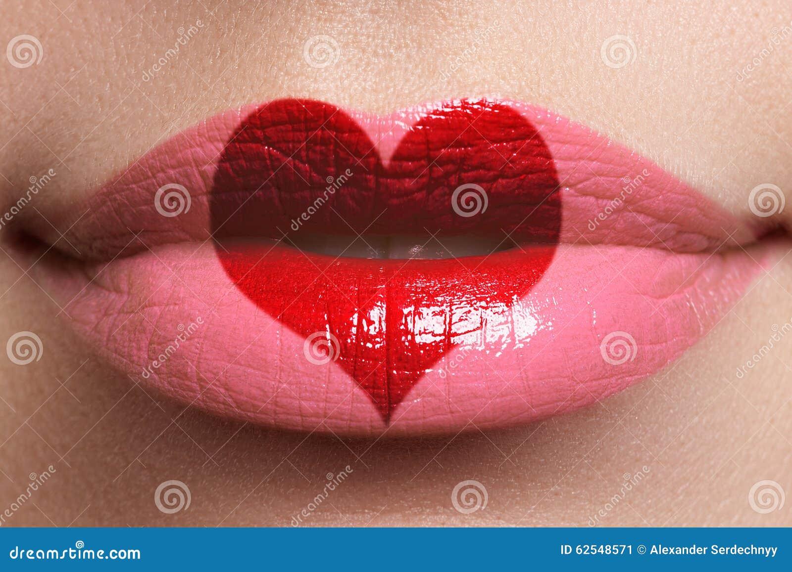 Beso del corazón en los labios Labios llenos atractivos de la belleza con la pintura de la forma del corazón Rose roja Maquillaje