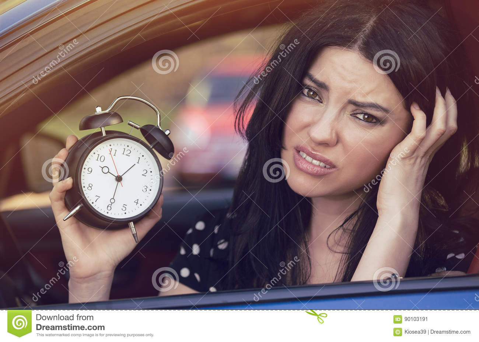 Besorgte Frau innerhalb des Autos, das den Wecker spät läuft, um zu arbeiten zeigt
