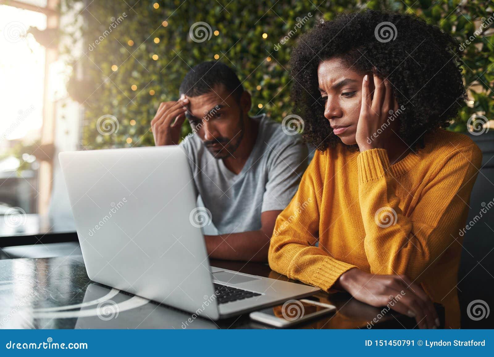 Besorgte junge Paare unter Verwendung des Laptops im Café
