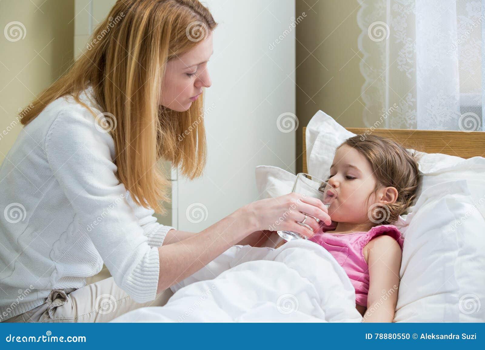 Besorgte Mutter, die ihrem kranken Kind Medizin gibt