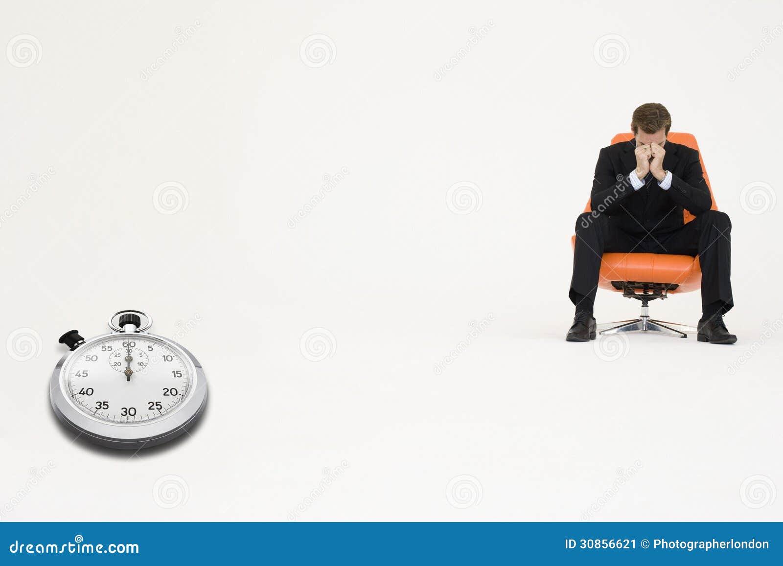 besorgter gesch ftsmann der auf stuhl mit der stoppuhr darstellt zeitverlust sitzt stockbild. Black Bedroom Furniture Sets. Home Design Ideas