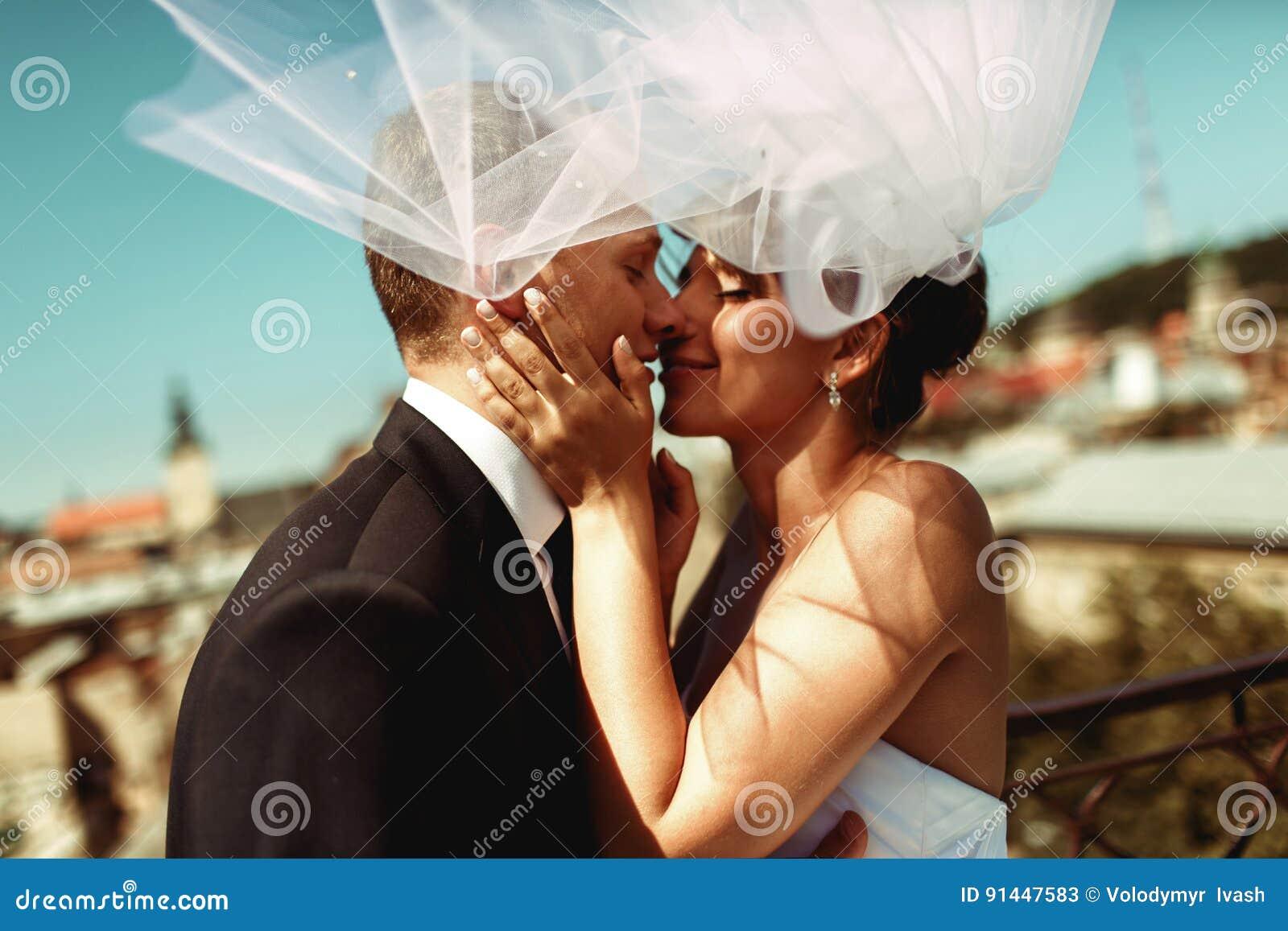 Besos de novia y del novio blando en la sombra de un velo del vuelo