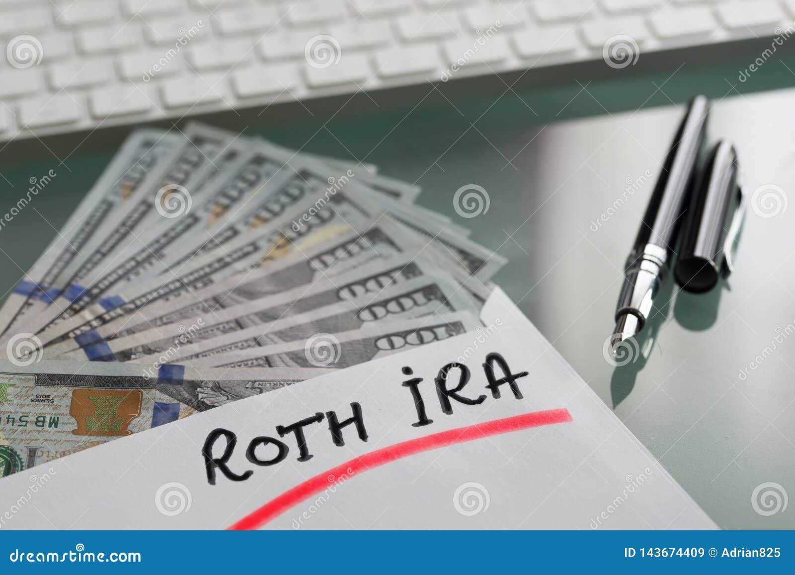 Besparingar för avgångbegrepp med Roth Ira som är skriftlig på det vita kuvertet med kassaUS dollar