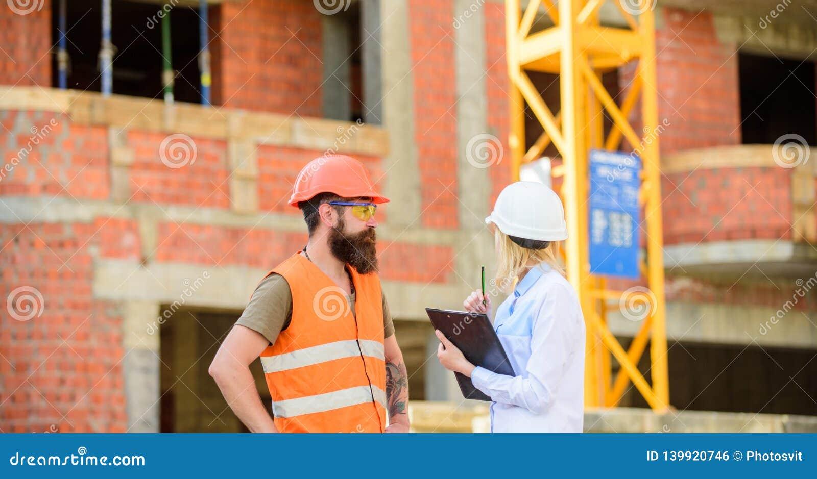 Bespreek vooruitgangsproject Het concept van de veiligheidsinspecteur De inspecteur en de gebaarde brutale bouwer bespreken bouwv