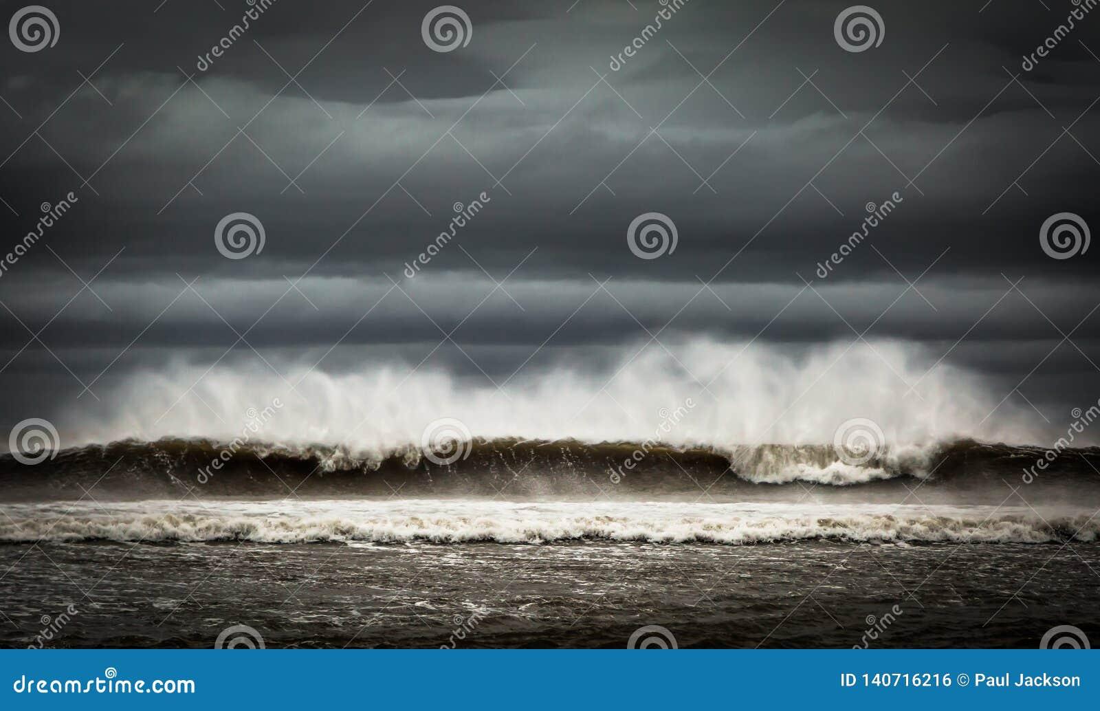 Bespruta att blåsas från stora vågor på en molnig dag