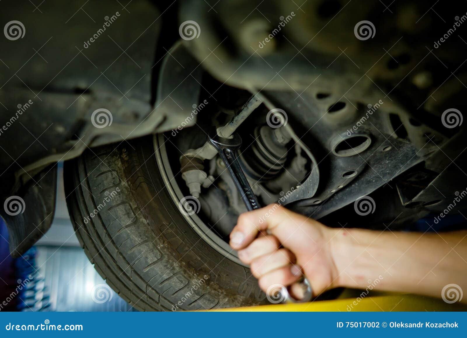Beståndsdel av den auto mekanikern som arbetar under en lyftbil