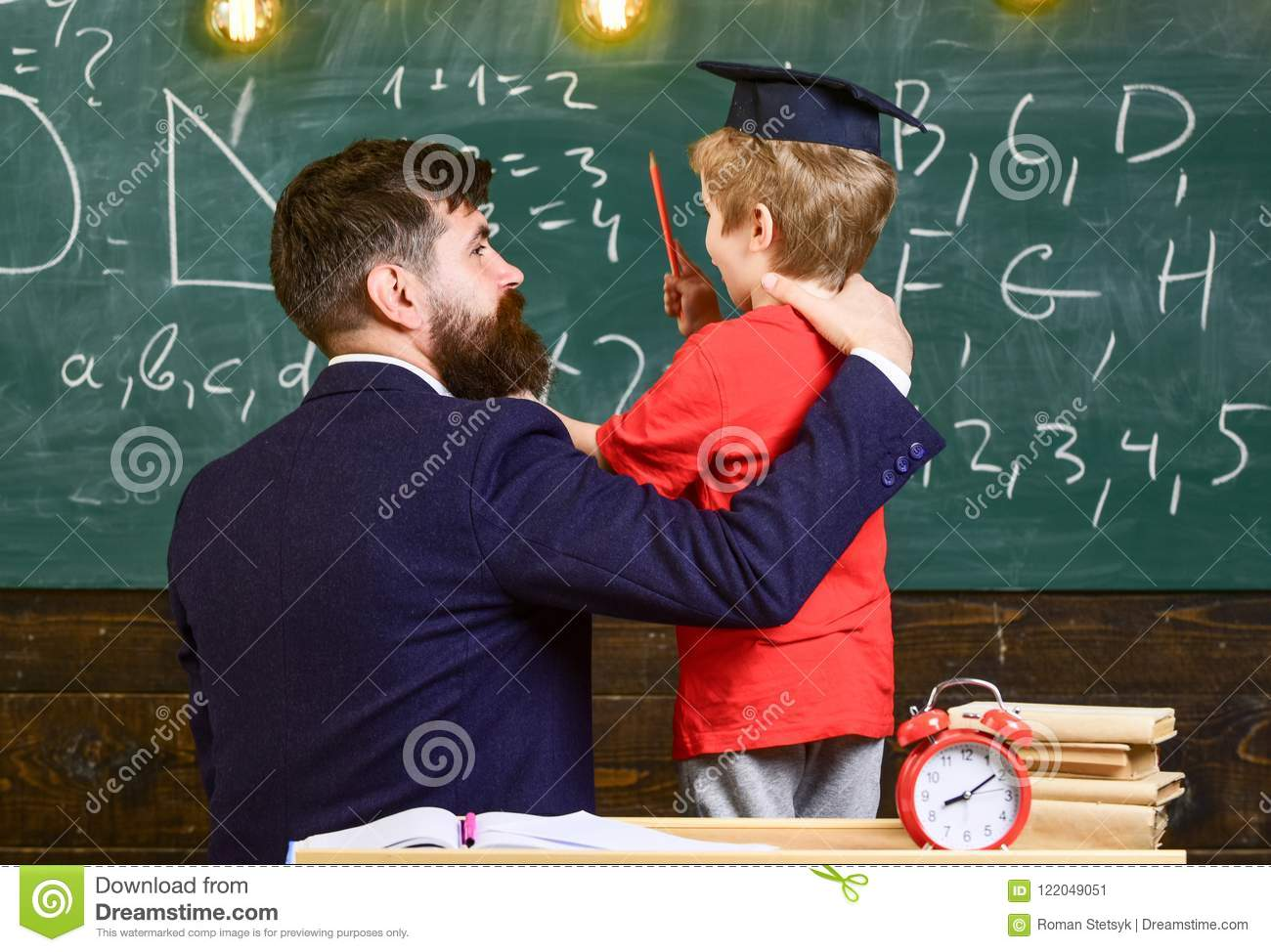 Best friends concept. Teacher with beard, father hugs little son in classroom while discussing, chalkboard on background