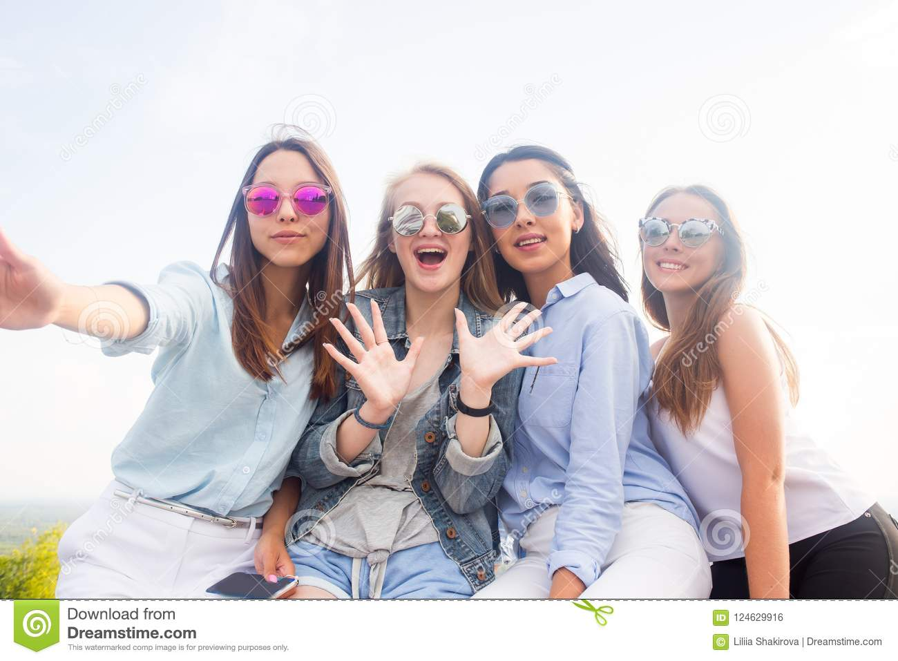 Best friends take selfies while walking in the Park. Four women wearing sunglasses are having a good day