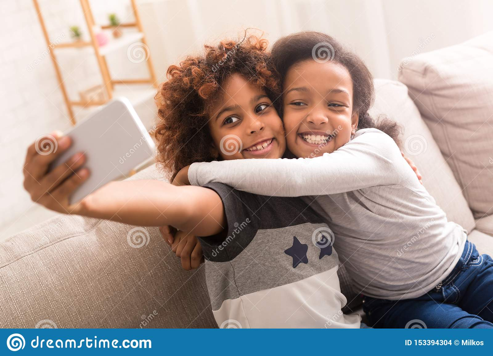 Best friends taking selfie on smartphone at home