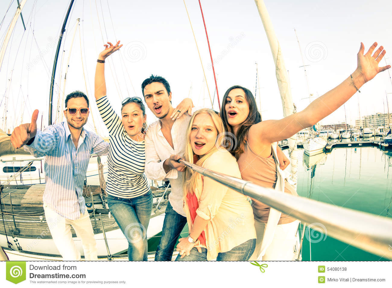 Best friends using selfie stick taking pic on exclusive sailboat