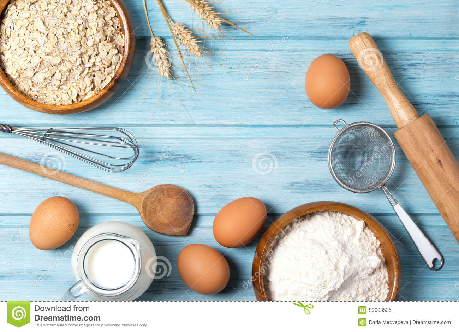 Bestandteile für das Backen, Milch, Eier, Weizenmehl, Hafer und Küchengeschirr auf blauem hölzernem Hintergrund, Draufsicht