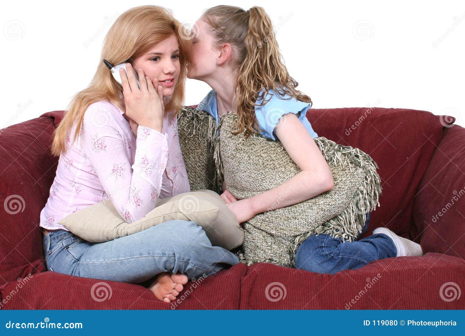 Beste Freunde, die am Telefon sitzt auf Couch klatschen