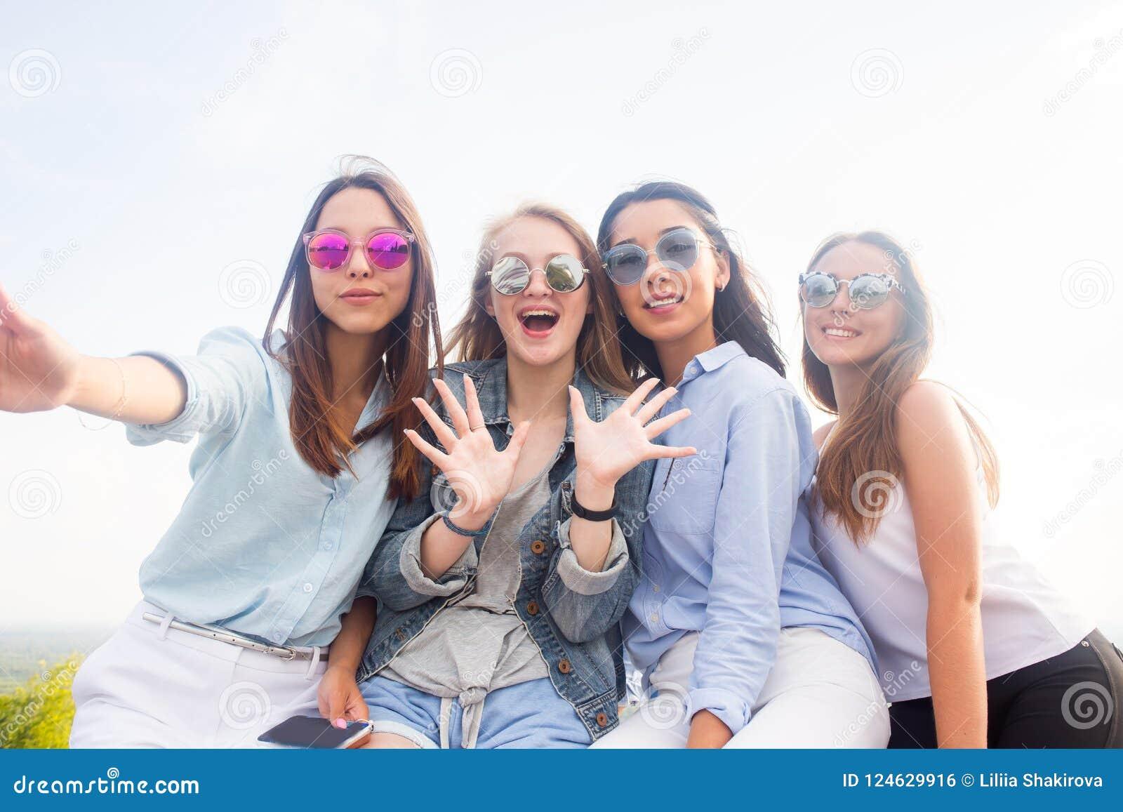 Beste Freunde nehmen selfies beim Gehen in den Park Vier Frauen, die Sonnenbrille tragen, haben einen guten Tag