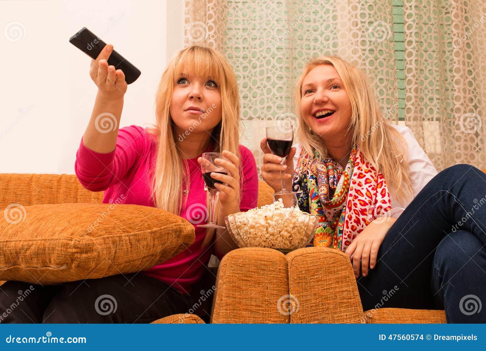 Beste vrienden die thuis op TV letten en wijn retro stijl gefiltreerd beeld drinken