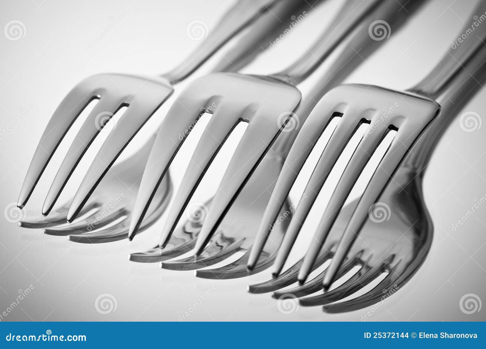 Bestek (vorken) op een spiegel in zwart-wit