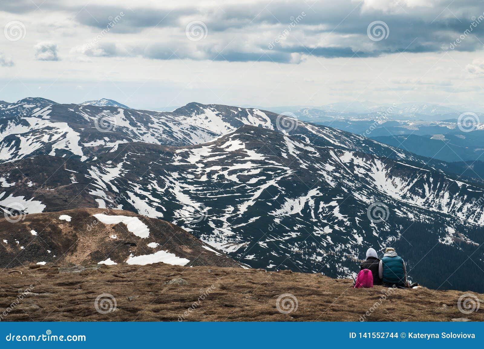 Bester Freund zwei auf dem Gras im See und im Berg sitzen