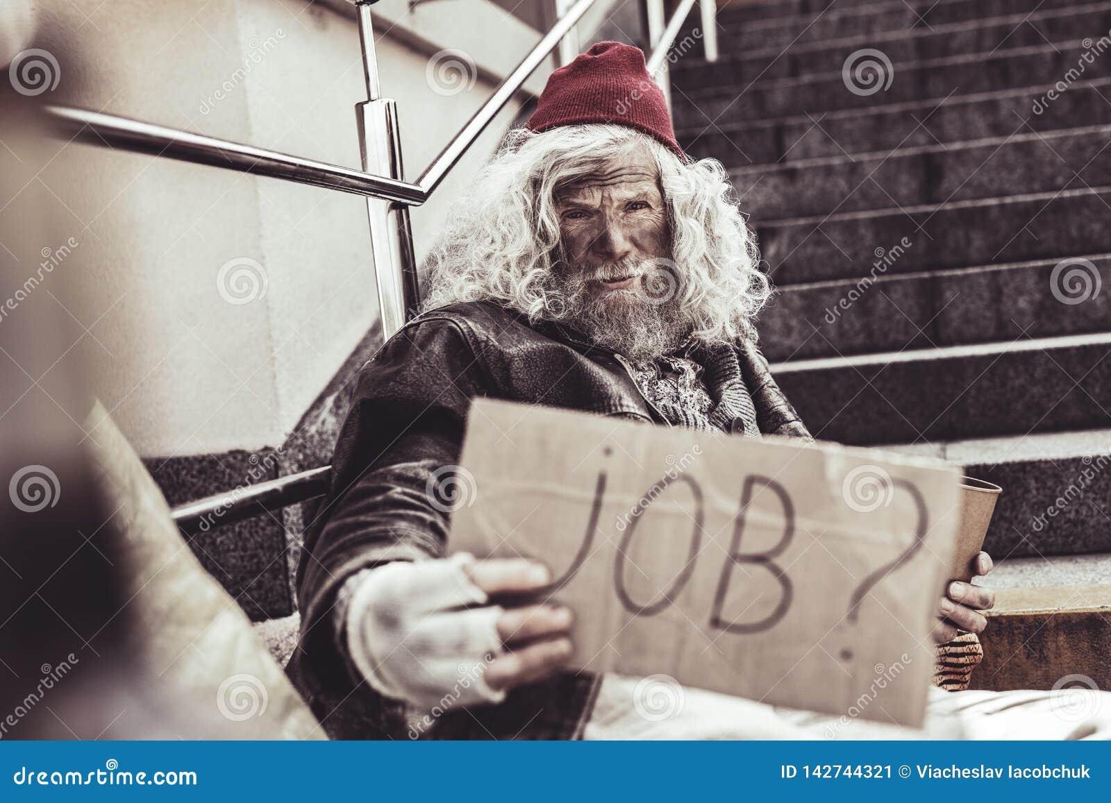 Besvärad almsman som frågar främling om något jobb för honom