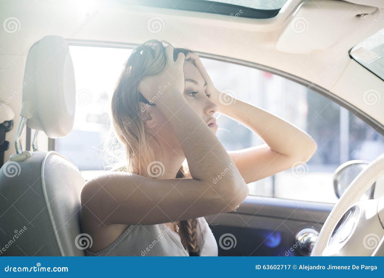 Besvärar på vägen, den trötta kvinnan trycker på hennes panna vid händer medan i en bil