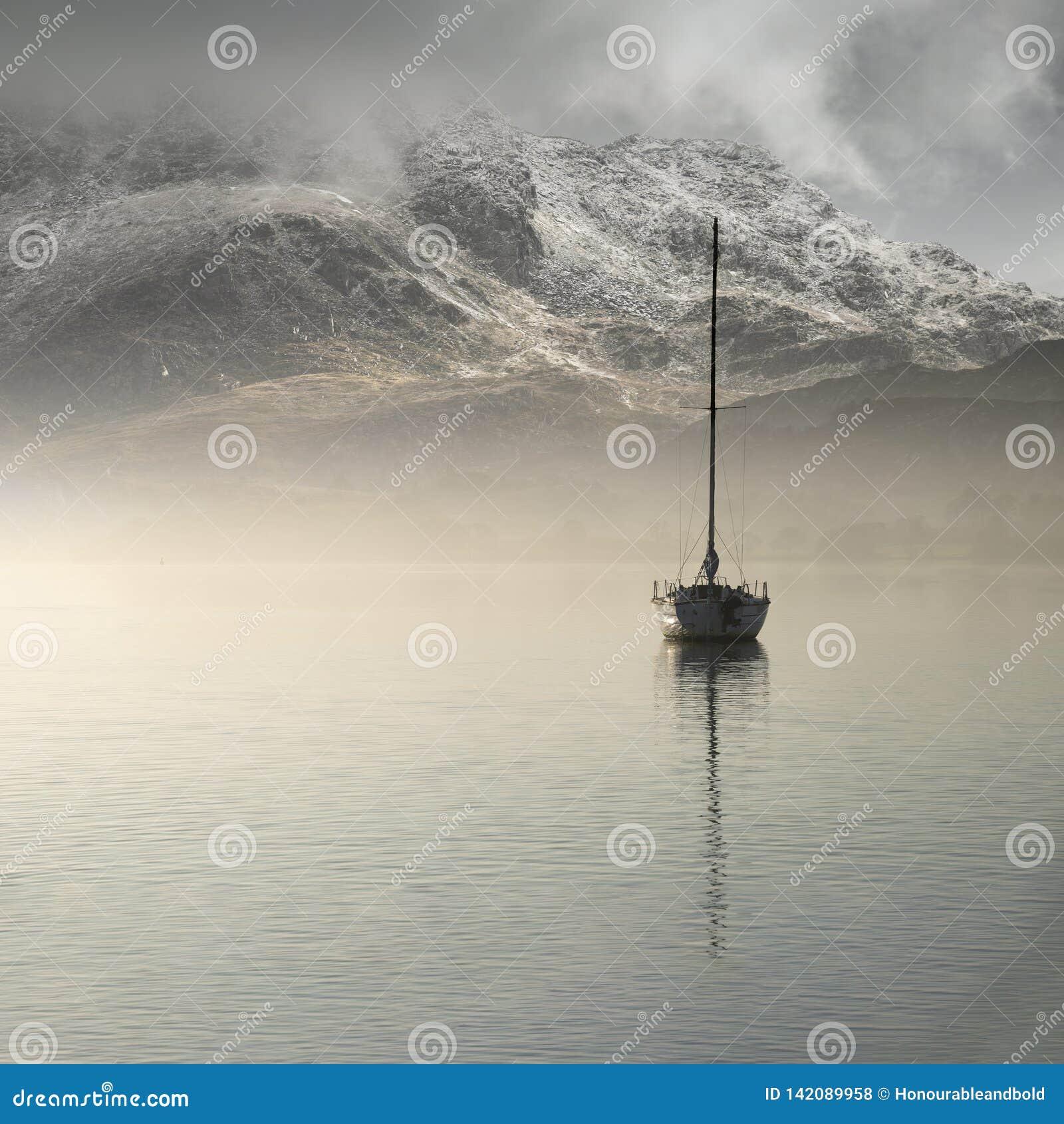Betäubungslandschaftsbild der Segeljacht noch sitzend im ruhigen Seewasser mit dem Berg, der im Hintergrund während Autumn Falls